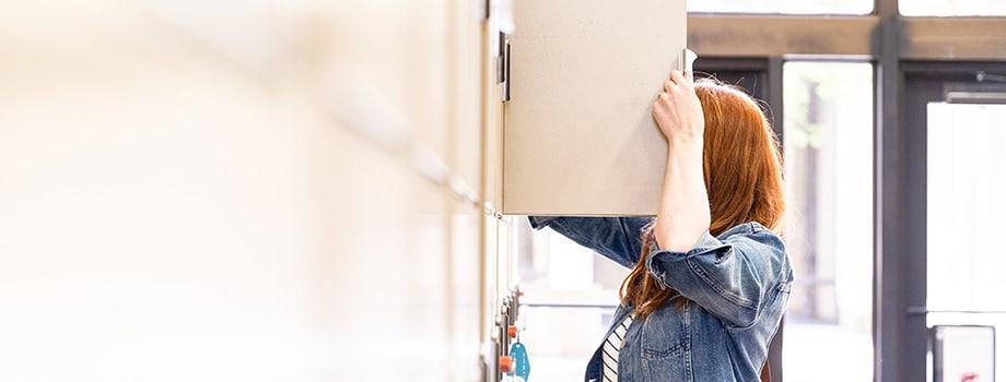 woman looking in kitchen cupboard. buying marijuana online.