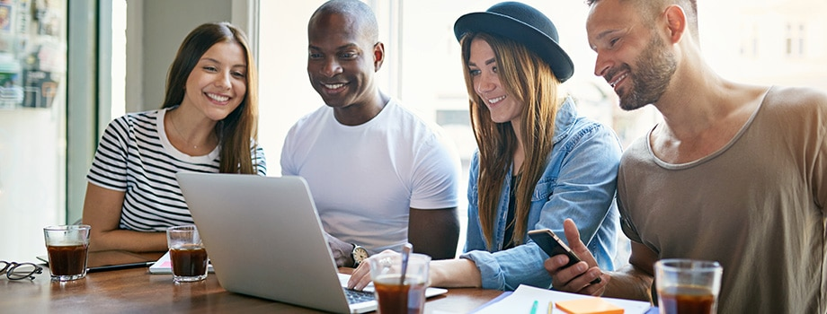Young adults at desktop smiling and working. How to buy weed online. mail order weed online in canada.