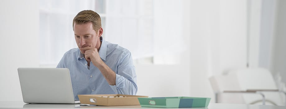 A man sitting at a desk using a laptop. where can i buy weed online?
