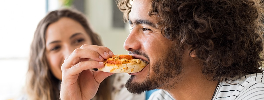 Man eating pizza. Where to buy marijuana edibles online. purchase weed edibles in Canada.