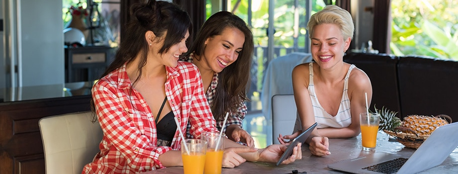 Three Women Sitting At Table Use Tablet Computer. Where to buy marijuana edibles online in Canada. Purchase THC edibles gummies gummy bears online.